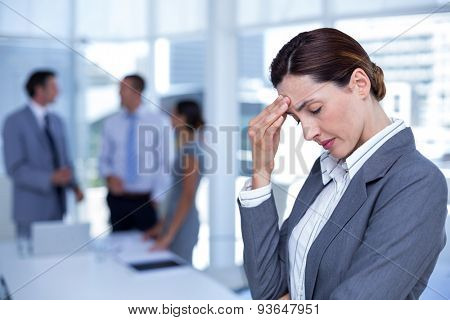 Worried businesswoman with head in one hand in an office