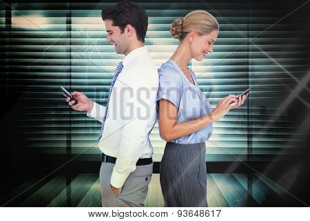 Business people using smartphone back to back against window overlooking city