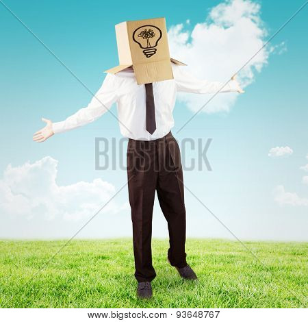 Anonymous businessman with arms out against blue sky over green field