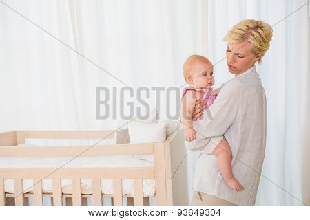 Beautiful mother holding her baby girl at home in bedroom