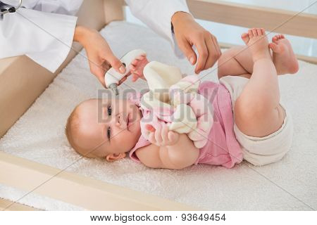 Beautiful cute baby girl with doctor taking temperature at home in bedroom
