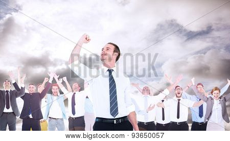 Businessman cheering with clenched fist against blue sky with white clouds