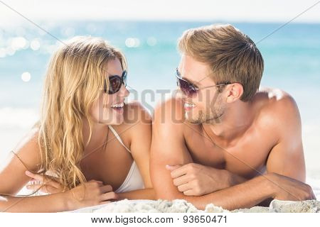 Happy couple relaxing together in the sand at the beach