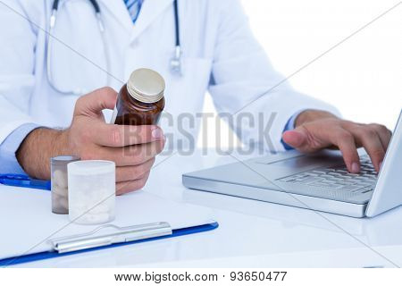 Close up plan of a doctor holding a medecine while typing on a laptop