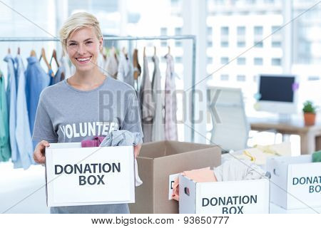 Smiling volunteer holding a box of donations in an office