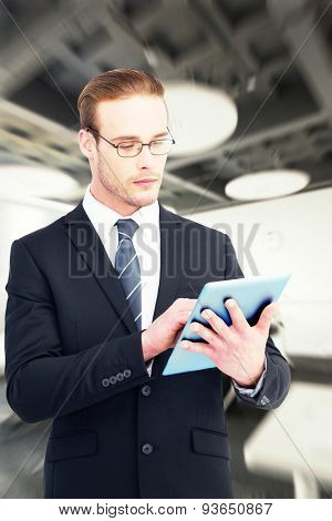 Unsmiling businessman using tablet pc against college classroom