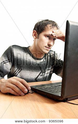 Hombre cansado se ve en la pantalla del ordenador portátil