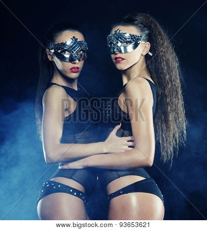 two young sexy striptease dancer with mask