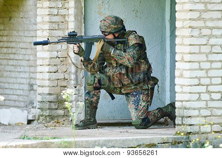 military. soldier with assault rifle at position in nato germany uniform with pistol indoord