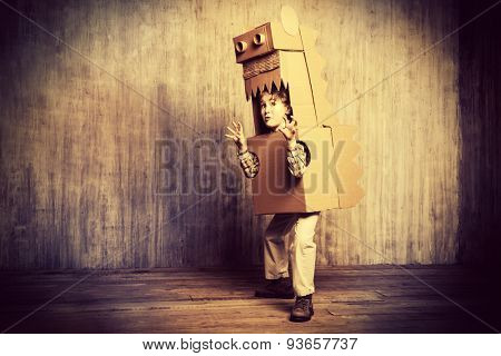 Funny dreamer boy playing with a cardboard dragon, dinosaur. Childhood. Fantasy, imagination. Retro style, sepia.