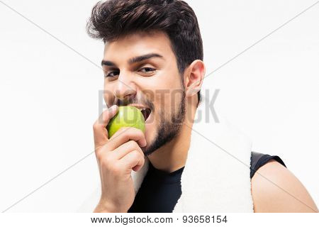 Fitness man with towel eating apple isolated on a white background