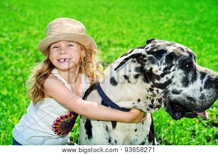 Happy little girl with her mastiff dog on a meadow in summer day.