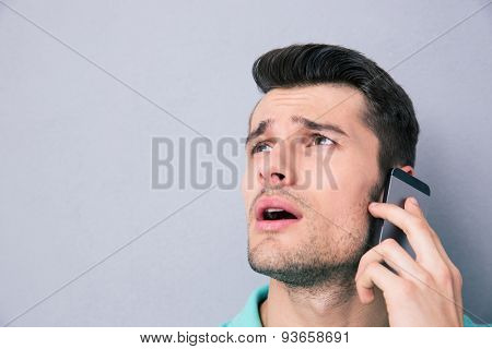 Closeup portrait of a pensive young man talking on the phone over gray background and looking up