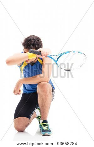 Tired sports man with tennis racket relaxing isolated on a white background