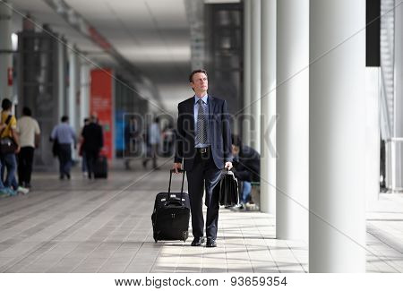 businessman walking with trolley through the crowd on a business travel