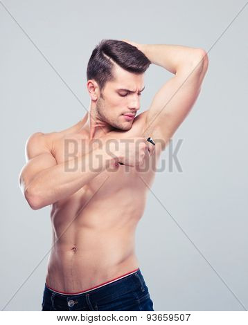 Handsome muscular man shaving his armpit over gray background