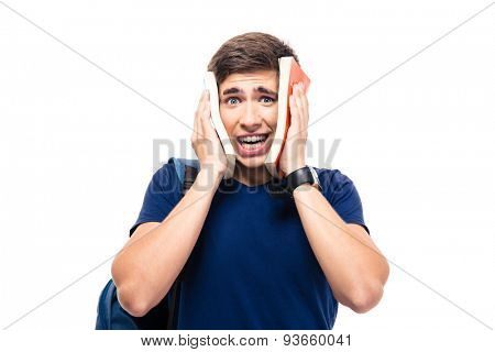 Male student covering his face with books isolated on a white background