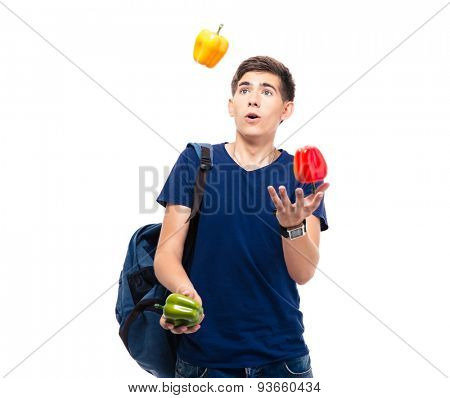 Casual young man juggles with pepper isolated on a white background