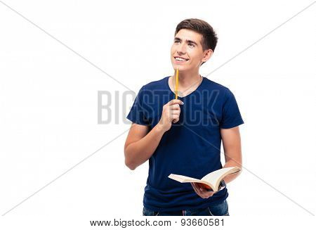 Happy thoughtful male student holding book looking up at copyspace isolated on a white background