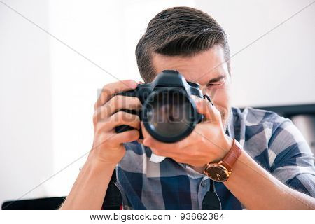 Casual man shooting with photo camera