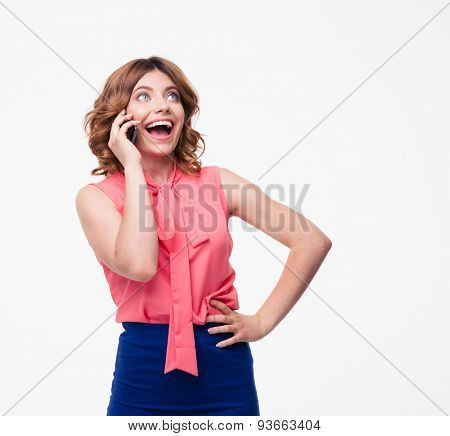 Cheerful woman talking on the phone isolated on a white background and looking up at copyspace