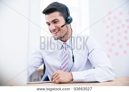 Portrait of a male operator with headset using PC in office