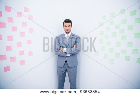 Handsome businessman with arms folded standing near wall with stickers in office