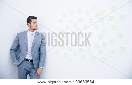 Businessman leaning on the wall and looking on stickers