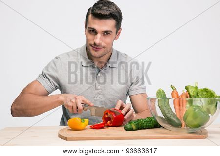 Handsome man preparing salad over gray background and looking camera