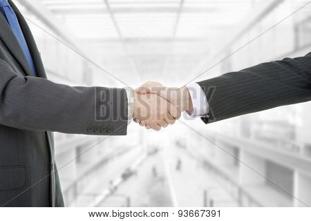Two businessmen handshake at the office
