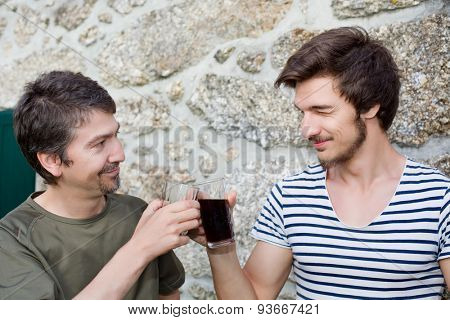 two friends having a drink and talking outdoors, focus on the man on the right