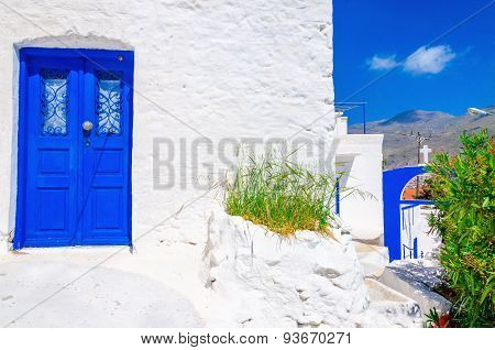 Blue wooden door, white wall and flowers in Greece
