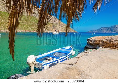 Blue and white wooden boat in cosy Greek port