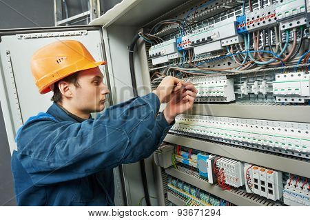 electrician with screwdriver tighten up switching electric actuator equipment in fuse box