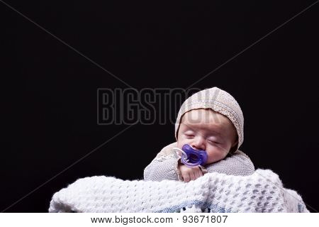 Newborn baby boy sleeping with a pacifier