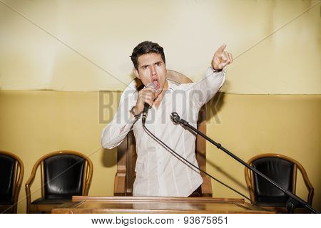 Passionate Man Speaking into Microphone in Meeting