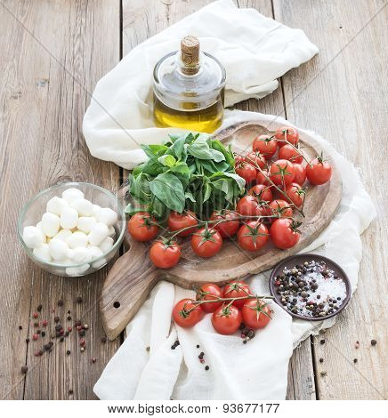 Basil, cherry-tomatoes, mozarella, olive oil,  salt, spices on rustic chopping board over old wood b