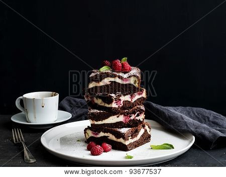 Brownies-cheesecake tower with raspberries on white ceramic plate