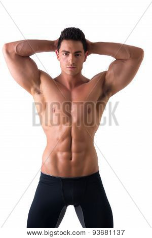 Muscular young man standing and looking at camera smiling