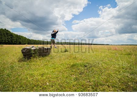 Kid playing outdoors. Boy jumping from stone