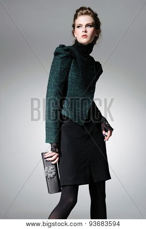 fashion model holding purse in light background