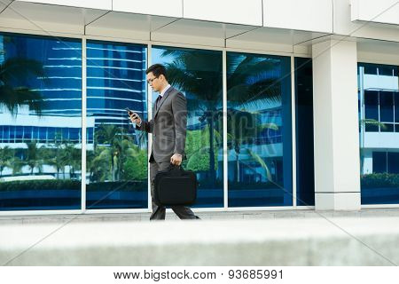 Businessman Reading Email On Mobile Phone Walking To Office