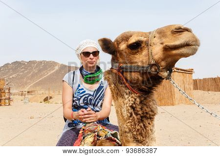 Young Caucasian Woman Tourist Riding On Camel