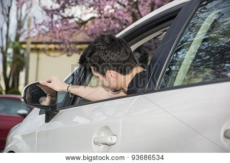 Young man in his car adjusting rear view mirror