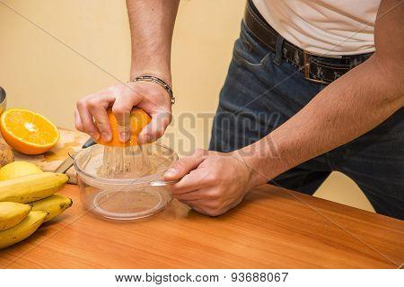 Young man squeezing orange