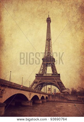 Eiffel tower view from Seine river, Paris, France.  Photo in  grunge and retro style.  Added paper texture