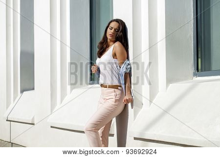 Beautiful young brunette woman in blue jeans jacket, against white wall