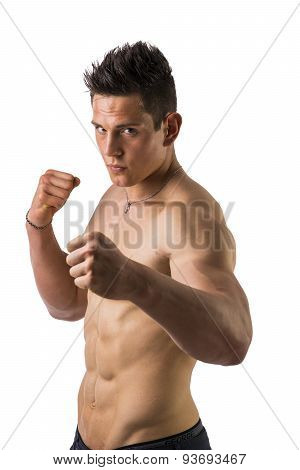 Shirtless male model throwing punch towards camera