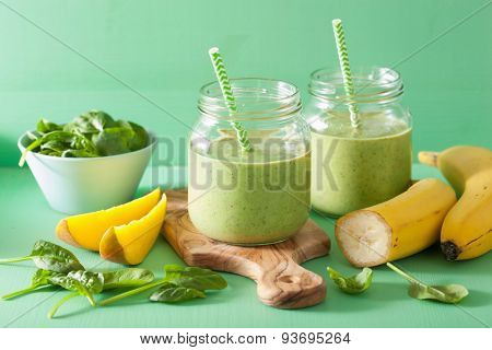 healthy green smoothie with spinach mango banana in glass jars
