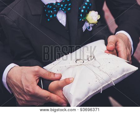 Father hands help young boy to carry a pillow with wedding rings during wedding ceremony